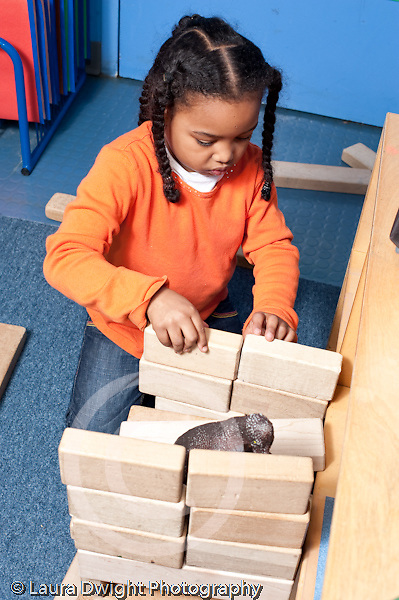 Educaton preschool 4-5 year olds block area girl working on construction made of wooden blocks plastic dinosaur inside vertical