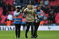 A fan takes a selfie as he is led away by stewards after invading the pitch at the final whistle during Tottenham Hotspur vs Leicester City, Premier League Football at Wembley Stadium on 10th February 2019