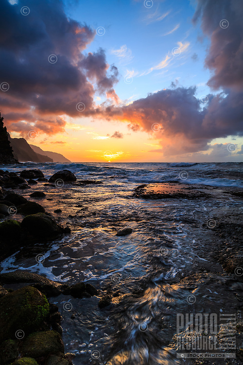 The sun sets on the Na Pali coastline while a dynamic ocean flows over a rocky reef at Ke'e Beach, Kaua'i.