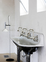 A trio of stainless steel taps have been fixed to a large black and white enamel trough to create a triple basin in the bathroom