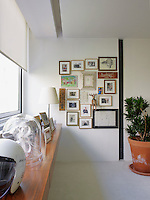 Family photographs are displayed alongside framed artwork on a wall of the bedroom