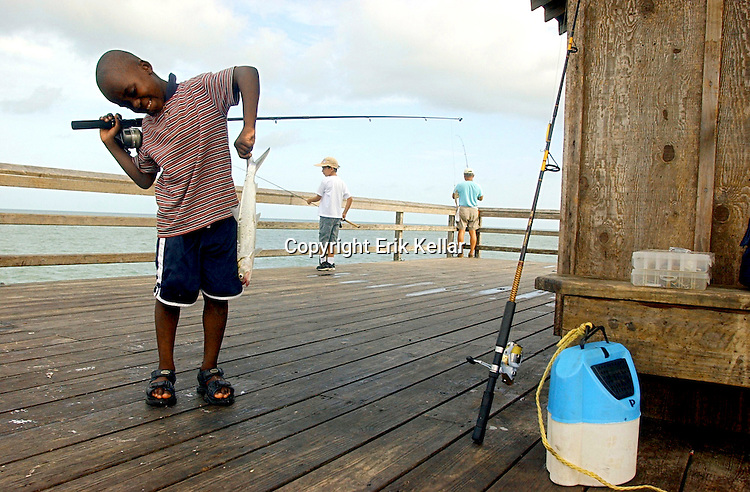 Cavy Joseph, 8, inspects a lady fish caught by another fisherman at the City of Naples Pier on Thursday. Joseph is part of the City of Naples Summer Camps weekly fish program. Each week a new group of kids, ages 6-13, learn how to bait a hook, cast a fishing pole and land a fish. Children are also taught how to identify fish as well as conservation efforts although children are able to keep what they have caught as long as the fish meets state size requirements. Fishing poles are not provided for the campers for the program which runs through the end of July. The rest of the summer is booked up but reservations will be accepted in the spring of 2004 for the following summer. For more information call Fleischmann Park at 213-3020. Erik Kellar/Staff..City of Naples Fishing Camp at Naples Pier on Thursday June 19. Erik Kellar/Staff 06/19/03