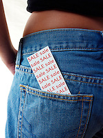 Close up of a  card with the words sale on it in the back pocket of blue jeans being worn by a women showing her bare waiste.