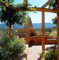 Stunning views across country to the mountains beyond from the terrace of a contemporary house in New Mexico where there is an outside oven and barbeque