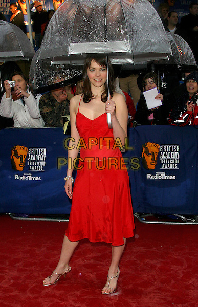 KATE FORD.BAFTA TV Awrds, Grosvenor House Hotel, London, .18th April 2004..full length raining wet red carpet umbrella red dress.Ref: BR.www.capitalpictures.com.sales@capitalpictures.com.©Capital Pictures.