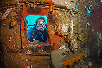 A female diver investigating the interior of a B-25 Mitchell Bomber plane wreck, Madang, Pacific Ocean, Papua New Guinea (MR), MR