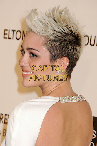 Miley Cyrus .21st Annual Elton John Academy Awards Viewing Party held at West Hollywood Park, West Hollywood, California, USA..February 24th, 2013.oscars headshot portrait white chains straps backless back behind rear looking over shoulder spiked platinum quiff dark buzzed roots hair dyed blonde earrings .CAP/ADM/BP.©Byron Purvis/AdMedia/Capital Pictures.