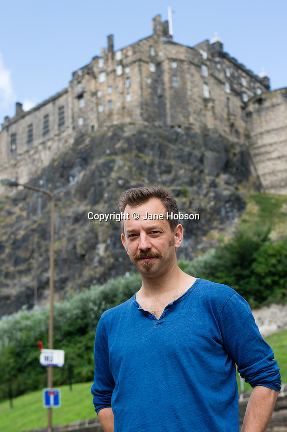 Edinburgh, UK. 16.08.2013. Joseph Alford, artistic director of Theatre O, beside the Castle, in Grassmarket. Joseph is directing THE SECRET AGENT, at the Traverse, as part of the Edinburgh Festival Fringe. The production is to transfer to London's Young Vic theatre. Photograph © Jane Hobson.
