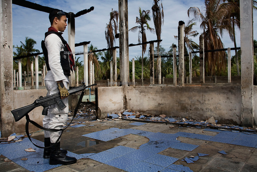 A thai policeman observes the remaining pieces of a school recently attacked by insurgents. Thailand is struggling to keep up appearances as the land of smiles has to face up to its troubled south. Since 2004 more than 3500 people have been killed and 4000 wounded in a war we never hear about. In the early hours of January 4th 2004 more than 50 armed men stormed a army weapons depot in Narathiwat taking assault rifles, machine guns, rocket launchers, pistols, rocket-propelled grenades and other ammunition. Arsonists simultaneously attacked 20 schools and three police posts elsewhere in Narathiwat. The raid marked the start of the deadliest period of armed conflict in the century-long insurgency. Despite some 30,000 Thai troops being deployed in the region, the shootings, grenade attacks and car bombings happen almost daily, with 90 per cent of those killed being civilians. 24.09.07. Photo: Christopher Olssøn.