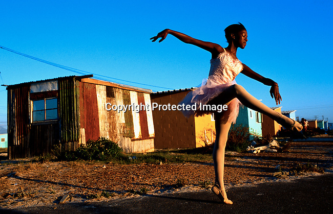Noluyanda Mqutwana, age 14, outside her family shack on January 30, 2000 in Khayelitsha, one of the poorest black townships outside Cape Town, South Africa. She's a very talented ballet dancer in the Dance for All project run by the Cape Town City Ballet. She has danced since 1996, she was among twelve talented students that got scholarships in 2000 to study at a mixed school, where they have ballet as a subject on a daily basis..Photo: Per-Anders Pettersson/Agentur Focus.