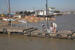 Mother and children crabbing from the jetty. Small fishing and sailing hamlet of Felixstowe Ferry at the mouth of the River Deben, Suffolk, England