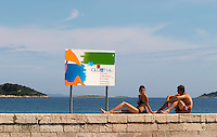 A young woman in bikini on a wall and a young man in swimming trunks, a sign saying Welcome to Croatia, on the beach by the blue sea, and island in the background Orebic town, holiday resort on the south coast of the Peljesac peninsula. Orebic town. Peljesac peninsula. Dalmatian Coast, Croatia, Europe.