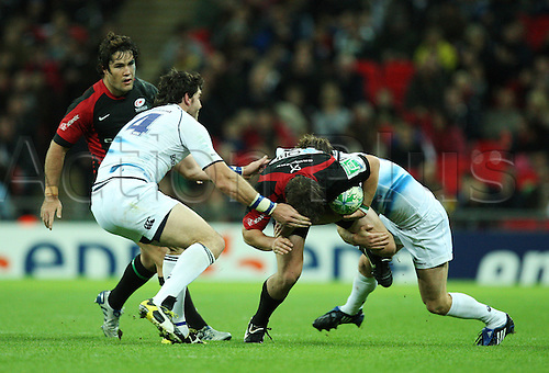 16.10.2010 Adam Powell (M) of Saracens tries to break the middle  while is tackles during the Heineken Cup Rugby match Saracens v Leinster at Wembley Stadium in London.