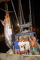 Bomboy Llanes (in blue), captain of the fishing boat Lana Kila, stands with the boat's crew next to a Pacific blue marlin grander, with angler Jen Brooks  and her husband Evan in background, Honokohau Harbor, Big Island.