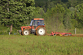 A farm tractor passing a disc harrow in a field