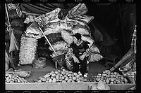 A woman sells potatoes at a local wet market in the  ancient city of Lijiang, Yunnan province, China, October 2013.