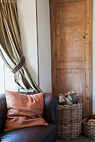 In the living room a comfortable brown leather sofa situated next to a built-in cupboard lovingly restored to its original patina