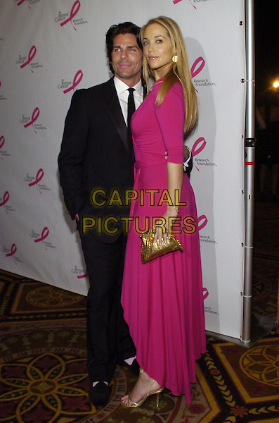 "GREG LAUREN & ELIZABETH BERKLEY  .Breast Cancer Reaserch Foundation's annual ""Hot Pink Party"" at the Waldorf-Astoria, New York, New York, USA..April 24th, 2007.full length hot pink dress bright gold clutch purse shoes bag wrap black suit  .CAP/ADM/BL.©Bill Lyons/AdMedia/Capital Pictures *** Local Caption ***"