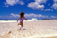 Little girl running through sea foam on the shore of a the beach on the north shore of Oahu.