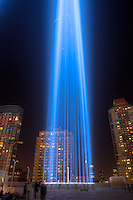 One of the beams of light of the Tribute in Light, an annual memorial to the events of September 11, 2001, shines into the night sky in New York City on Tuesday, September 11, 2012 from the installation on the roof of the Battery Parking Garage on West Street above the entrance to the Battery Tunnel.  The streaks of light visible inside the beams are birds flying in the lights.