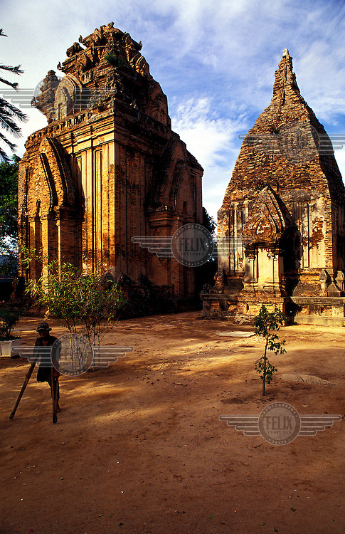 Man on crutches passes ancient stupa complex near to the central Vietnamese coastal city of Nha Trang.  Credit: Chris Stowers.