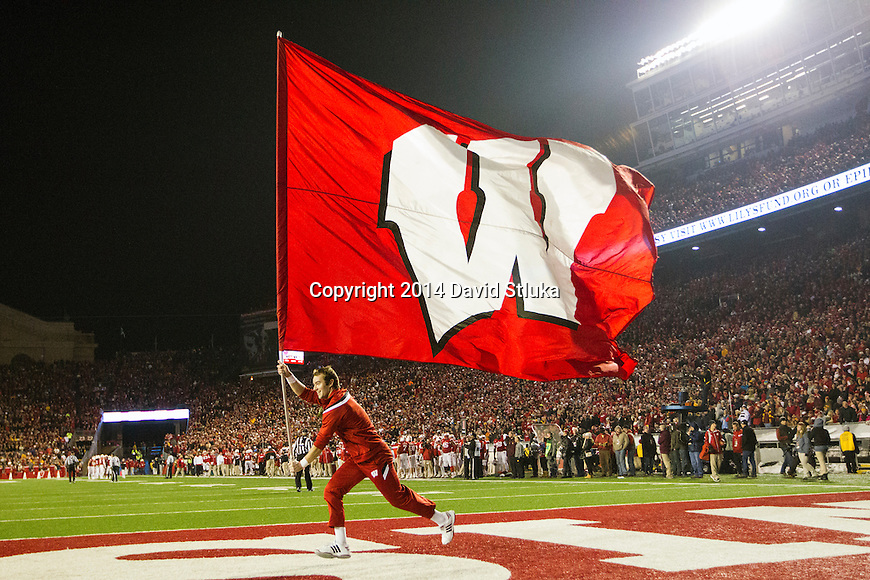Wisconsin Badgers cheerleader runs with the Motion W flag during an NCAA Big Ten Conference football game against the Minnesota Golden Gophers Saturday, November 29, 2014, in Madison, Wis. The Badgers won 34-24. (Photo by David Stluka)