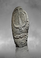 Late European Neolithic prehistoric Menhir standing stone with carvings on its face side. The representation of a stylalised male figure starts at the top with a long nose from which 2 eyebrows arch around the top of the stone. below this is a carving of a falling figure with head at the bottom and 2 curved arms encircling a body above. at the bottom is a carving of a dagger running horizontally across the menhir.  Excavated from Barrili II site,  Laconi. Menhir Museum, Museo della Statuaria Prehistorica in Sardegna, Museum of Prehoistoric Sardinian Statues, Palazzo Aymerich, Laconi, Sardinia, Italy