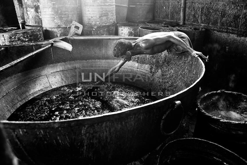 A man collects oil from the wastage lather at Hazaribagh tannery area in Dhaka, Bangladesh.  This oil will be used for making soap.