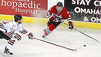 St. Cloud State's Jared Festler tries to control the puck while being pressured by Nebraska-Omaha's Brian O'Rourke. Nebraska-Omaha defeated St. Cloud State 4-3 Saturday night at CenturyLink Center in Omaha. (Photo by Michelle Bishop) .