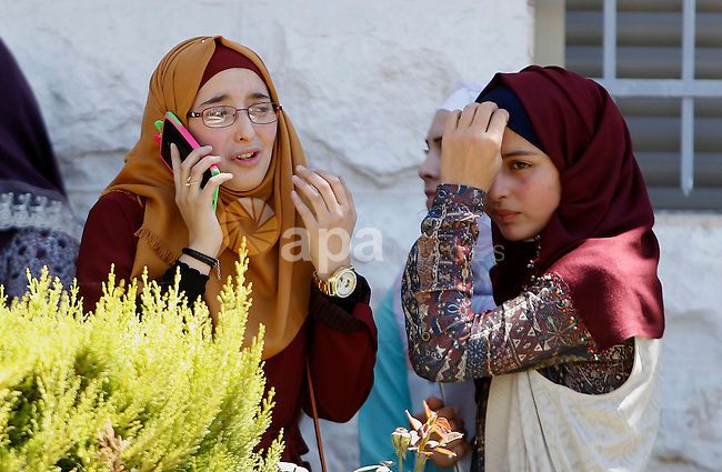 """Palestinian high school students celebrate after heard their results of final exams known as """"Tawjihi"""", in the West Bank city of Hebron on July 11, 2016. Photo by Wisam Hashlamoun"""