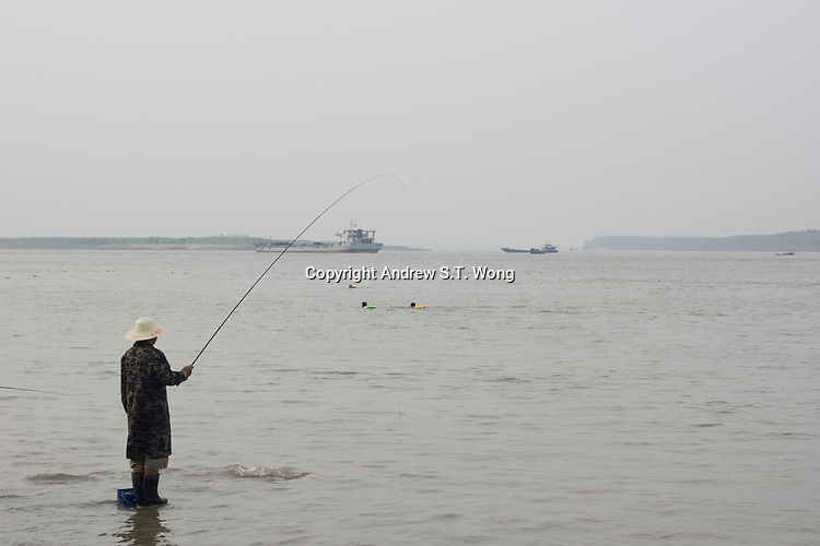Huanggang, Hebei province, China - An angler casts a line at the Yangtze River, October 2014.