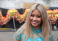 Beautiful blonde Asian woman wearing turquoise blue traditional dress,  Dragon Fest, Chinatown, Seattle, WA, USA.