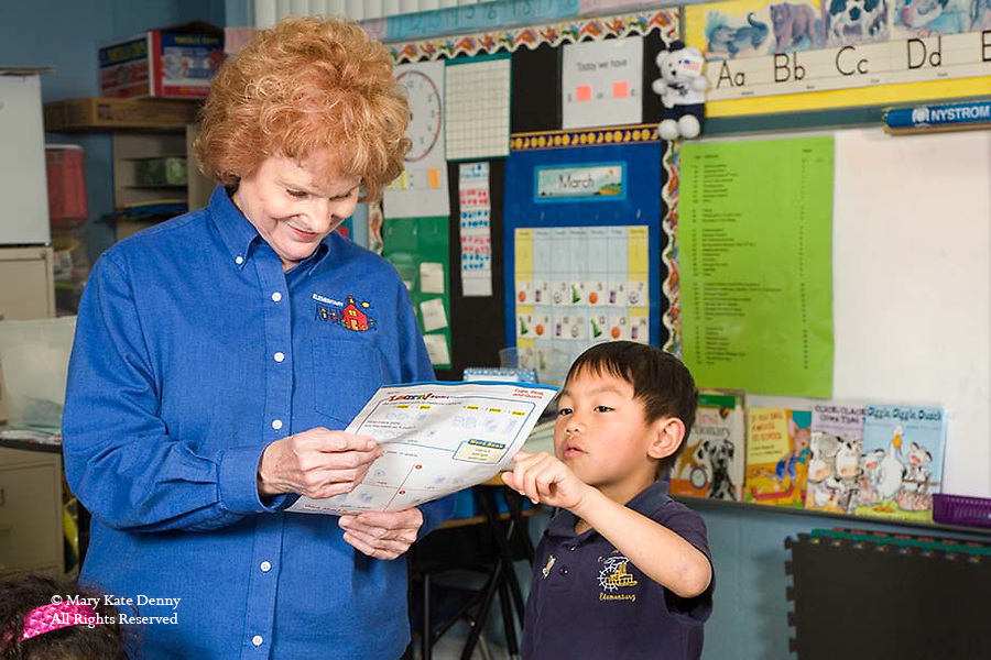 Caucasian red headed teacher smiles as she checks paper work of Vietnamese American seven year old boy in classroom in New Orleans