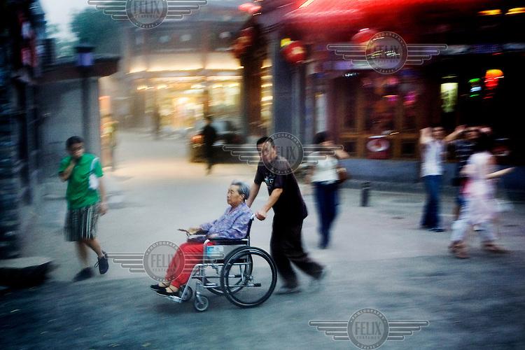 A man pushes an elderly woman in a wheelchair along a street in Beijing.