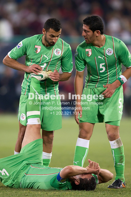 PRETORIA, SOUTH AFRICA - JUNE 23:  Algeria players Nadir Belhadj (3) and Rafik Halliche (5) assist teammate  Anther Yahia (4) late in a 2010 FIFA World Cup Group C match against the USA June 23, 2010 at Loftus Versfeld Stadium in Pretoria, South Africa.  Editorial use only.  No mobile use.    (Photograph by Jonathan P. Larsen)