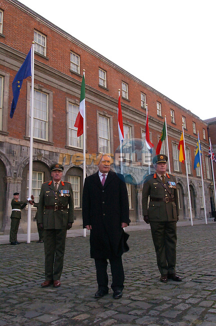 (Irish Prime Minister) Taoiseach Bertie Ahern standing for photographers at the opening ceremony of Ireland sixth Presidency of the European Union, as the European Flag is raised in the Background, Flanked on his right is Leut. General Colm Mangan chief of the defence forces. And left General officer Commanding Eastern Brigade Brigadier General Gerard McNamara. in Dublin Castle, Dublin Ireland on 1st January 2004.AFP PHOTO/NEWSFILE/FRAN CAFFREY