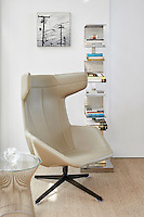 A leather chair placed in one corner with a floor-standing shelf unit to one side and a Warren Platner side table to the other. Neutral tones combine with natural materials and textures such as leaher and cool metals.