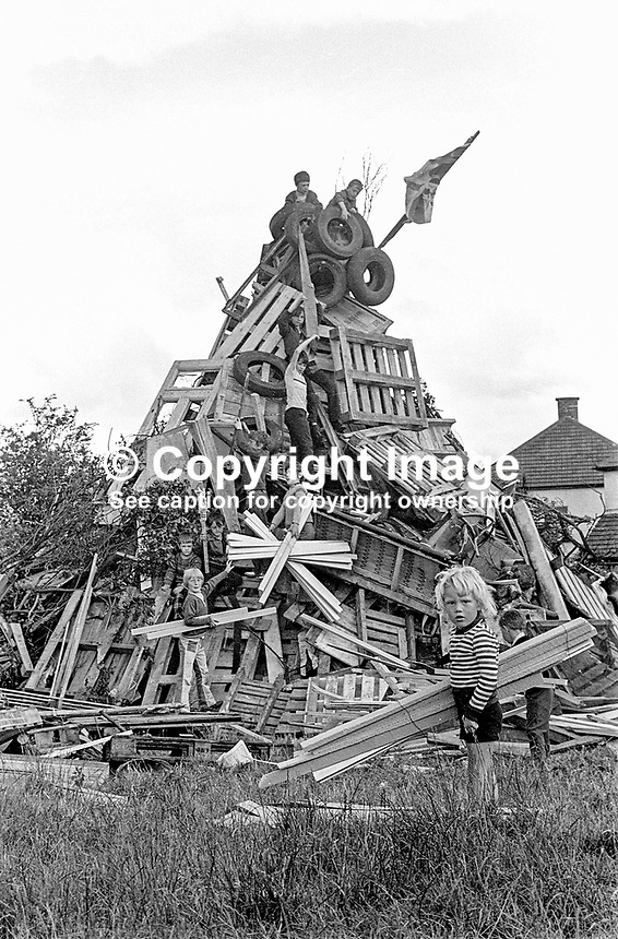 Children building a traditional Eleventh Night bonfire on a Belfast housing estate, N Ireland, UK. The widespread bonfires are a precursor to the Orangemen's Twelfth of July parades the following day. 1974071103871/3, 387/74.<br />
