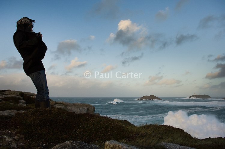 A young woman braves the gale and storm force winds which create breakers, waves and rough seas off the north end of the island of Tresco, Isles of Scilly, Cornwall, UK.  The lighthouse on Round Island is in the distance.  03/12/06