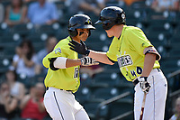 Shortstop Andres Gimenez (13) of the Columbia Fireflies is greeted by Ian Strom after scoring a run in a game against the Rome Braves on Sunday, August 20, 2017, at Spirit Communications Park in Columbia, South Carolina. Rome won, 11-6 in 16 innings. (Tom Priddy/Four Seam Images)