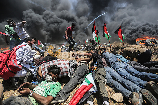 "Palestinian protesters gather during clashes with Israeli security froces in a tent city protest where Palestinians demand the right to return to their homeland, on the occasion of the 70th anniversary of the ""Nakba"", and against U.S. embassy move to Jerusalem at Israel-Gaza border at the Israel-Gaza border, in Khan Younis in the southern Gaza Strip on May 14, 2018. Photo by Ashraf Amra"