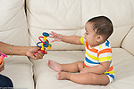 7 month old baby boy sitting reaching for toy with straight back