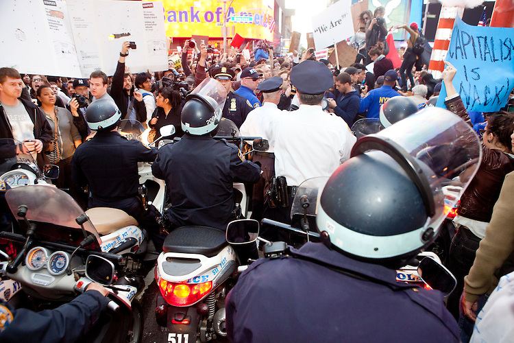 """Policemen on scooters futilely try to control a crowd of protesters with """"Occupy Wall Street"""" at Times Square on October 15, 2011 in New York City.  While crowd estimates numbered in the tens of thousands, police tactics (including nets, motor scooters, barricades, arrests, and intimidation by riders on horseback) prevented the crowd, which had been split up, from joining together as one in the middle of Times Square."""