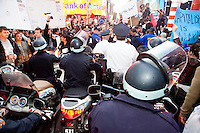 "Policemen on scooters futilely try to control a crowd of protesters with ""Occupy Wall Street"" at Times Square on October 15, 2011 in New York City.  While crowd estimates numbered in the tens of thousands, police tactics (including nets, motor scooters, barricades, arrests, and intimidation by riders on horseback) prevented the crowd, which had been split up, from joining together as one in the middle of Times Square."
