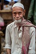 A man sits for a photograph at a market stall in Kolkata, India, on Saturday, May 27, 2017. Photographer: Sanjit Das