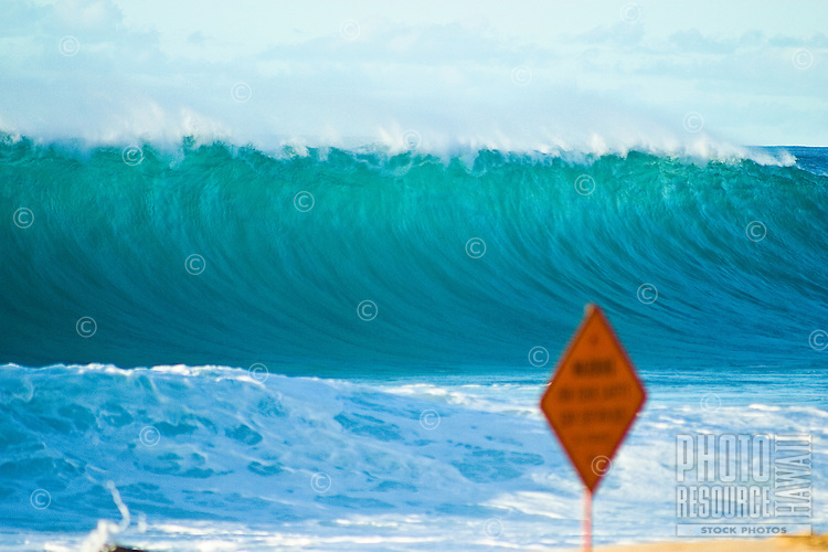 Large wave about to break at Rock Piles on the north shore of Oahu. Out of focus dangerous surf warning sign in foreground.