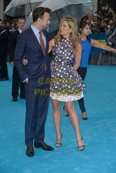Jason Sudeikis, Jennifer Aniston<br /> 'We're the Millers' European UK film premiere, Empire cinema, Leicester Square, London, England.<br /> 14th August 2013<br /> full length blue pink white sleeveless floral print dress suit red tie hand in pocket profile <br /> CAP/PL<br /> &copy;Phil Loftus/Capital Pictures