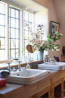 In the mullioned window of this bathroom a matching pair of basins has been placed on a contemporary wooden washstand