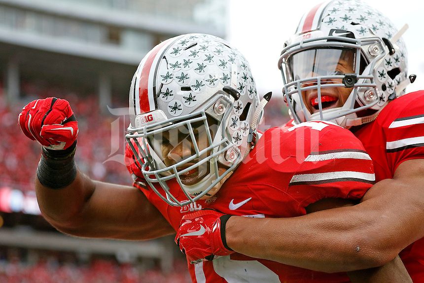 Ohio State Buckeyes running back Ezekiel Elliott (15) celebrates his 44-yard touchdown run on fourth down with teammate Ohio State Buckeyes wide receiver Evan Spencer (6) during the fourth quarter of the NCAA football game against Michigan at Ohio Stadium on Saturday, November 29, 2014. (Columbus Dispatch photo by Jonathan Quilter)