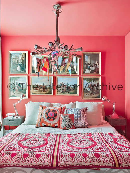 The bedroom is an eclectic and exotic mix with deep coral pink walls, a collection of 19th century Spanish paintings, a 20th century chandelier festooned with bunting and patterned bedding